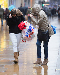 © London News Pictures. 23/12/2013 . London, UK.  Christmas shoppers brave strong winds and heavy rain on Oxford Street, central London. Heavy rain and strong winds are disrupting road, rail and sea travel ahead of the Christmas break in parts of the UK. Photo credit : Ben Cawthra/LNP