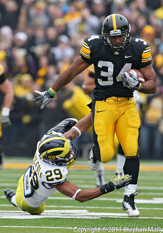 November 05, 2011: Iowa Hawkeyes running back Marcus Coker (34) pulls away from Michigan Wolverines cornerback Troy Woolfolk (29) on a run during the second quarter of the NCAA football game between the Michigan Wolverines and the Iowa Hawkeyes at Kinnick Stadium in Iowa City, Iowa on Saturday, November 5, 2011. Iowa defeated Michigan 24-16.