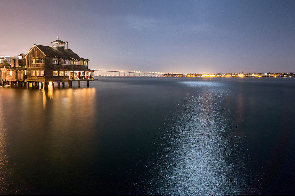 fisherman's wharf in San Diego, CA. Shot at night with moonlight reflecting off the water and Coronado Bridge in background