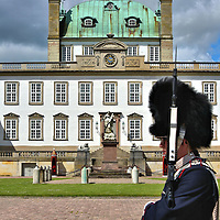 Royal Life Guard at Fredensborg Palace in Fredensborg, Denmark<br /> When Queen Margrethe is in residence at the Fredensborg Palace, the property is protected by the Royal Life Guards.  The distinguished dark blue uniform of Den Kongelige Livgarde is accented by a white slash and the traditional bearskin hat. There is a changing of the guard ceremony every day at noon. For a special treat, plan your visit on Thursday when a drums and fifes regiment marches into the courtyard and conducts a concert.
