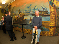 Wayne Fletcher stands proudly in front of the Moulton Opera House curtain on public display at the Laconia Library.  (Karen Bobotas/for the Laconia Daily Sun)