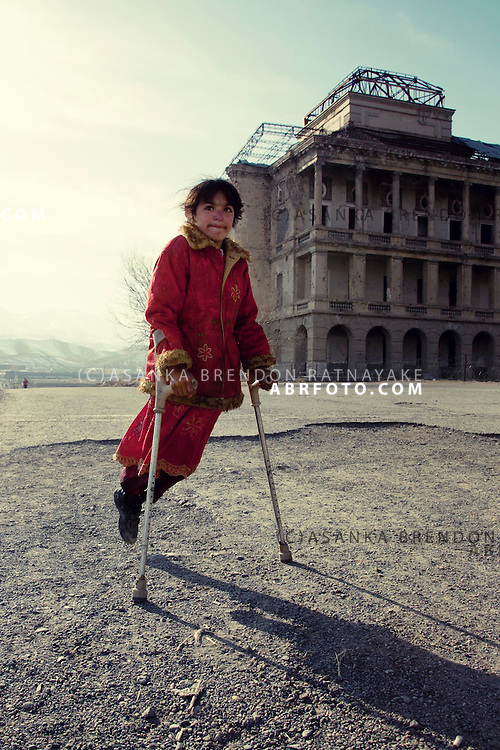 A young girl on crutches walks past the Darul Aman Palace in Kabul Afghanistan