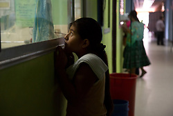 "Rosario, 14, peers into the neonatal ICU of Hospital San Benito. ""Our girls believe they were brought into this world to be a mother,"" said Dr. Daniel Alvarez a pediatrician at the hospital. ""When she is 12 she is used to raising her siblings. She doesn't go to school, she is not literate. Some of these girls don't even learn Spanish, they only use their mother language. At a certain age, the only escape in their mind is to get involved with a boy, and do the same thing… be a mother, be part of the cycle. That's the cycle we are trying to break. We need to give more power to women to make good choices."""