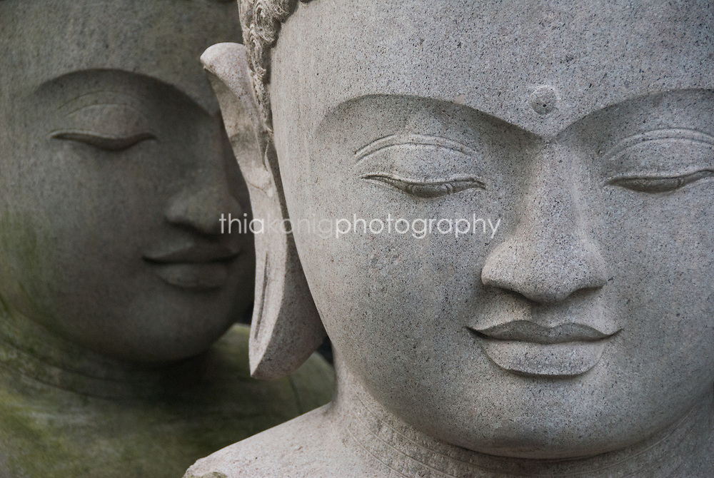 Two carved stone Buddha statues are positioned such that they look as if they are whispering to each other, Bali.