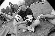 Playful blonde female sitting crossed legged in the park. Moss Side Carnival, Alexandra Park, Manchester 1989