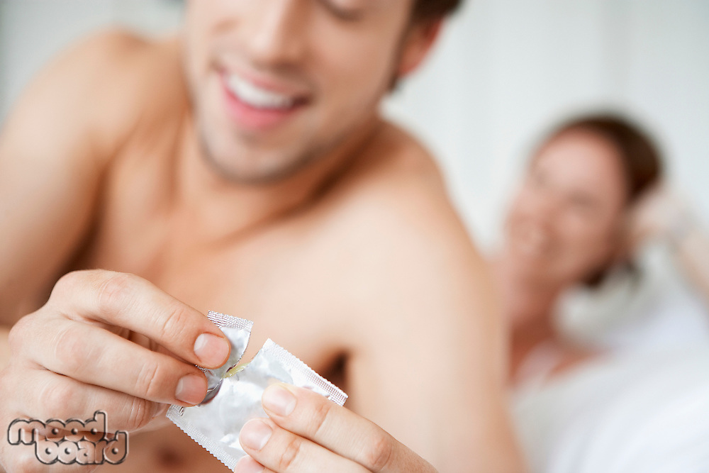 Couple in bed man opening condom close up of condom