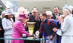 Queen Elizabeth II presents the trophy for the Diamond Jubilee Stakes to jockey Tom Queally after winning with The Tin Man during day five of Royal Ascot at Ascot Racecourse.