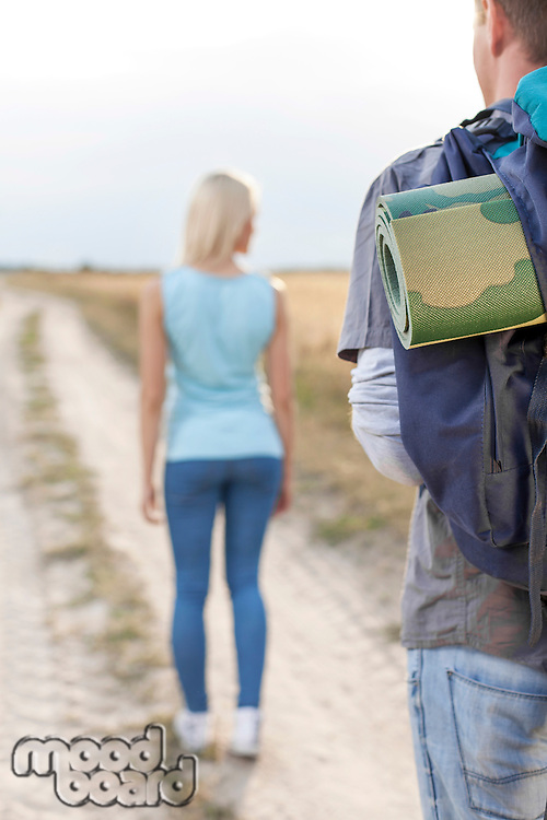 Male hiker carrying backpack with woman walking in foreground on field