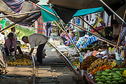 17 JANUARY 2013 - SAMUT SONGKHRAM, SAMUT SONGKHRAM, THAILAND: A man shops for fruit in the market in Samut Songkhram. Four trains each day make the round trip from Baan Laem, near Samut Sakhon, to Samut Songkhram, the train chugs through market eight times a day (coming and going). Each time market vendors pick up their merchandise and clear the track for the train, only to set up again when the train passes. The market on the train tracks has become a tourist attraction in this part of Thailand and many tourists stop to see the train on their way to or from the floating market in Damnoen Saduak.    PHOTO BY JACK KURTZ