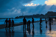 People on the seafront at the Grand Plage, as Atlantic waves lash the resort town of Biarritz, in the Basque region of France, March 2013