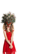 Portrait of girl in red outfit wearing peacock mask over white background