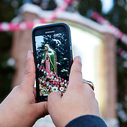 Taking time for a picture with a smart phone during the Feast Our Lady of Guadalupe celebration annual two-day feast celebration of Mexico's patron saint. Braving extremely cold temperatures, believers from the Chicago area and other parts of the United States gather day and night to pay homage at the shrine.   Photography by Jose More