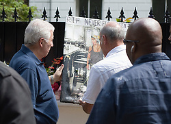 © licensed to London News Pictures.  28/07/2011. London, UK. Mitch Winehouse (left) taking a picture of amy Winehouse left by a fan, from outside Amy's home today (28/07/2011). family and freinds visited the late singers home to removed items belonging to Amy. Photo credit: Ben Cawthra/LNP