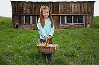 Girl (5-6) holding egg basket at farm portrait