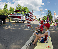 Karter and Kaden sit along the curb as boats and floats make their way down North Main Street towards Opechee Park during the 4th of July parade Thursday afternoon.  (Karen Bobotas/for the Laconia Daily Sun)
