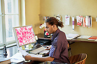Young man reading papers near computer in office