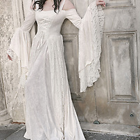 A young woman in a fancy white historical wedding dress in a marble palace