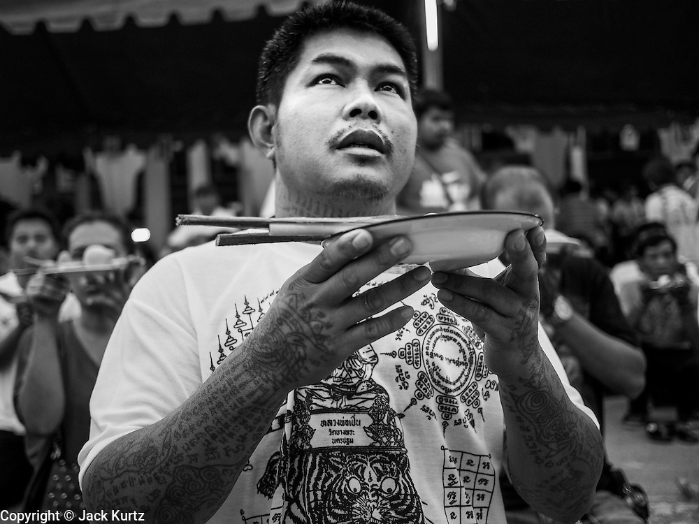 "15 MARCH 2014 - NAKHON CHAI SI, NAKHON PATHOM, THAILAND: A man prays at the beginning of the Wat Bang Phra tattoo festival. Wat Bang Phra is the best known ""Sak Yant"" tattoo temple in Thailand. It's located in Nakhon Pathom province, about 40 miles from Bangkok. The tattoos are given with hollow stainless steel needles and are thought to possess magical powers of protection. The tattoos, which are given by Buddhist monks, are popular with soldiers, policeman and gangsters, people who generally live in harm's way. The tattoo must be activated to remain powerful and the annual Wai Khru Ceremony (tattoo festival) at the temple draws thousands of devotees who come to the temple to activate or renew the tattoos. People go into trance like states and then assume the personality of their tattoo, so people with tiger tattoos assume the personality of a tiger, people with monkey tattoos take on the personality of a monkey and so on. In recent years the tattoo festival has become popular with tourists who make the trip to Nakorn Pathom province to see a side of ""exotic"" Thailand.   PHOTO BY JACK KURTZ"