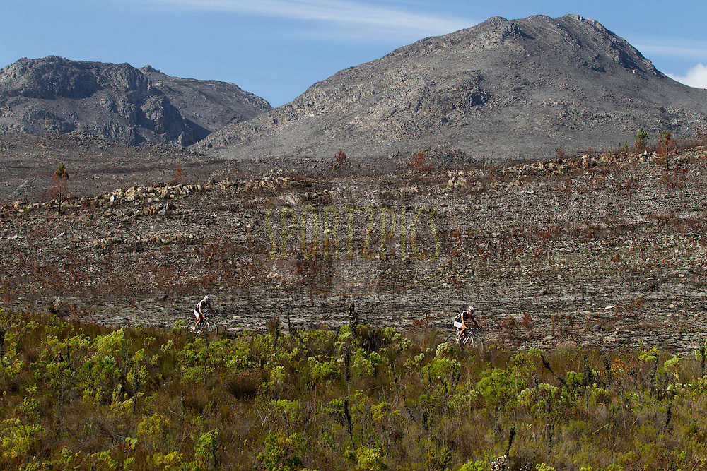 Riders pass a burnt area near Caledon during stage 4 of the 2012 Absa Cape Epic Mountain Bike stage race held at the Overberg Primary & High School in Caledon, South Africa on the 29 March 2012..Photo by Greg Beadle/Cape Epic/SPORTZPICS