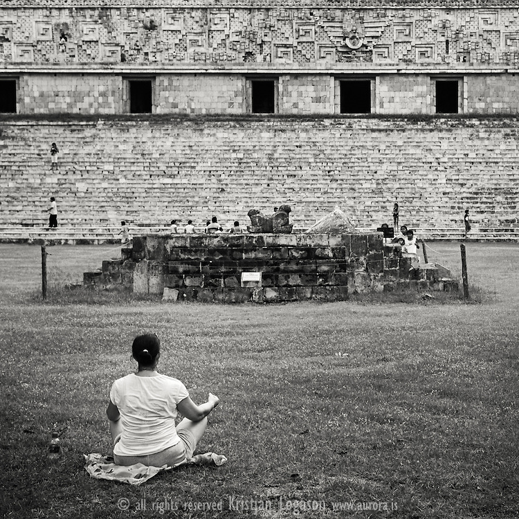 Woman meditatin on the grass field in front of the pyramids in Uxmal. Uxmal  is an ancient Mayan city of the classical period. Today is one of the most important archaeological sites of Mayan culture. For mor images from Mexico see www.aurora.is