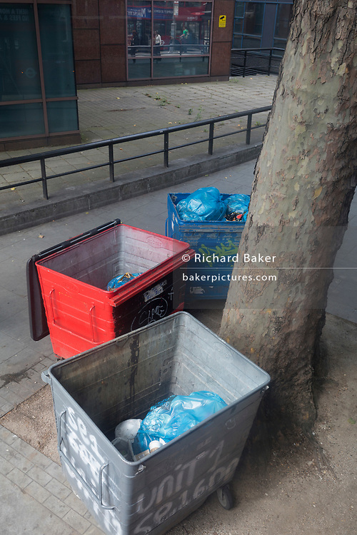Waste bins beneath an urban tree at Elephant & Castle in the south London borough of Southwark, on 5th August 2019, in London, England