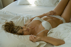 Young woman in white lingerie relaxing in bed