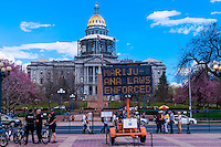 "Denver Police stand near one of the entrances (and electronic billboards stating ""Marijuana Laws Enforced"" (with the Colorado State Capitol in back) to the 420 Cannabis Culture Music Festival, Civic Center Park, Downtown Denver, Colorado USA. This was the first 4/20 celebration since recreational pot became legal in Colorado January 1, 2014. A crowd of up to 80,000 people attended the event."