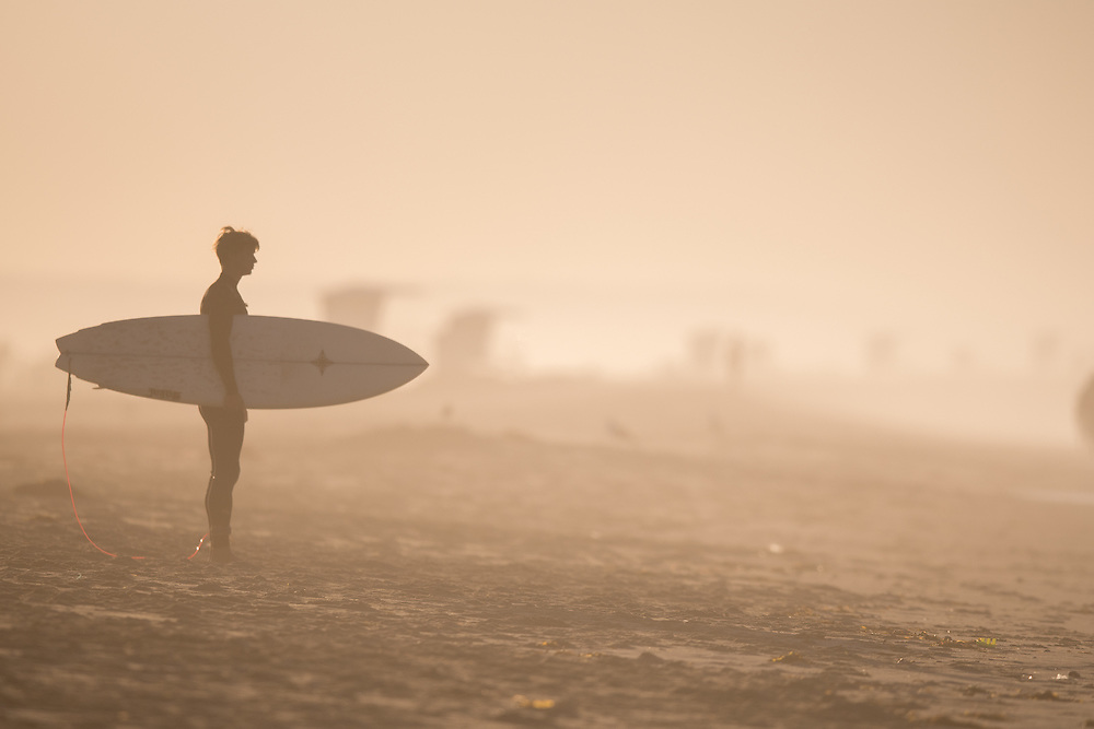 11/3/16 7:51:20 AM --- A surfer prepares for an early morning session close to the Huntington Beach Pier --- Huntington Beach, CA. Photo by Colter Peterson/ Sports Shooter Academy