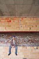 Construction worker sitting on brick wall