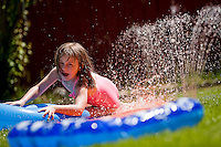 "JEROME A. POLLOS/Press..Sophia Pennings, 5, skims across the surface of a ""slip n' slide"" Thursday in front her home in Coeur d'Alene. City of Coeur d'Alene monthly water consumption user fees increased June 1 to 67 cents from 65 cents per thousand gallons up to 30,000 gallons per month for single-family residences."