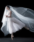 Classical ballet dancer in a Giselle costume, in a white skirt, shot in the studio on a black background. Photograph taken in New York City by Rachel Neville.
