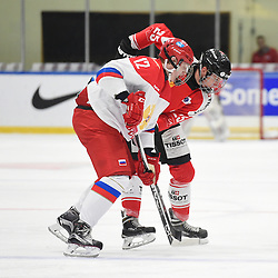 WHITBY, - Dec 15, 2015 -  WJAC Game 6- Team Russia vs Team Switzerland at the 2015 World Junior A Challenge at the Iroquois Park Recreation Complex, ON. Artem Ivanyuzhenkov #12 of Team Russia battles for control with Nando Eggenberger #25 of Team Switzerland during the second period.<br /> (Photo: Andy Corneau / OJHL Images)