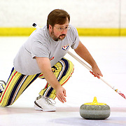 Roger White delivers a stone during a curling match at the Wilmington Ice House. (Jason A. Frizzelle)