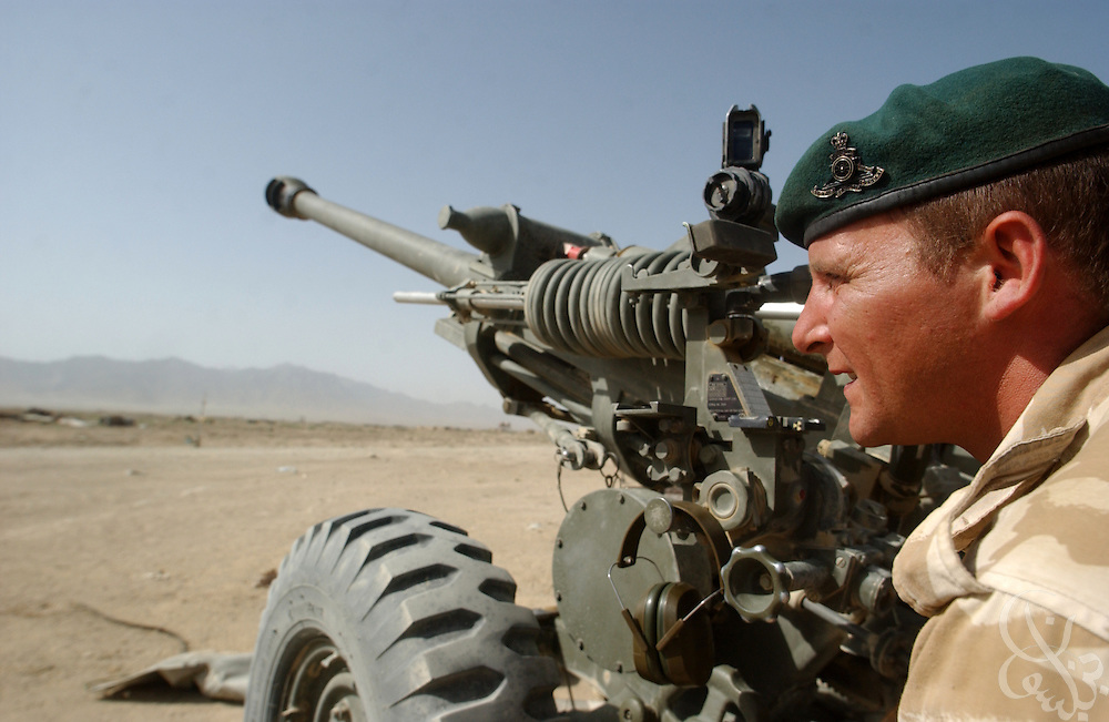 A British soldier looks downrange as British and American forces prepare to fire 105mm artillery rounds during a live fire exercise June 11, 2002 at Bagram Airbase in Afghanistan. Coalition troops continue to train for missions in Afghanistan as part of Operation Enduring Freedom.