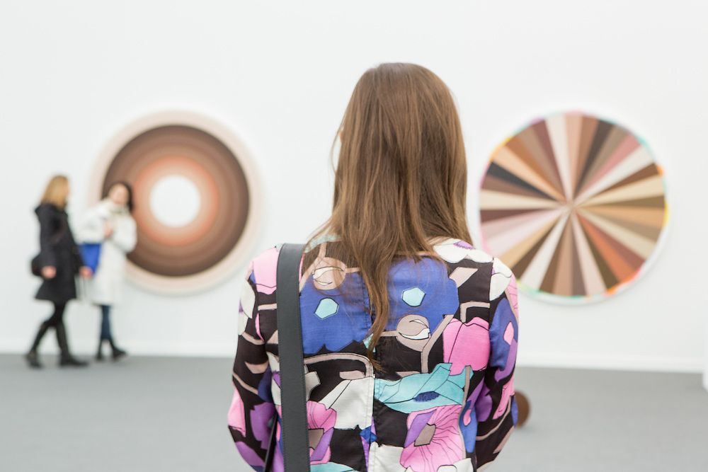 New York, NY - 6 May 2016. Frieze New York art fair. A woman in a colorful jacket looking at Adriana Varejão's Big Polvo Color Wheel II and -III in Galeria Fortes Vilaça.