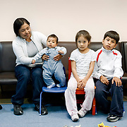 Milan, Italy, May 2008. Centre for immigrant women's health, San Carlo Hospital. Juana, Bolivian mother and her three kids: Giacomo, Wendy and Luis-Alberto, waiting for the pediatrc visit...Milano, Italia, Maggio 2008. Centro di salute e ascolto donne immigrate, Ospedale San Carlo. Juana, mamma boliviana, con i tre figli Giacomo, Wendy e Luis-Alberto in attesa della visita pediatrica.......