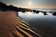 Tidal pool and sand ripples on an incoming tide at sunset at Porth Swtan, Church Bay, Anglesey, Wales
