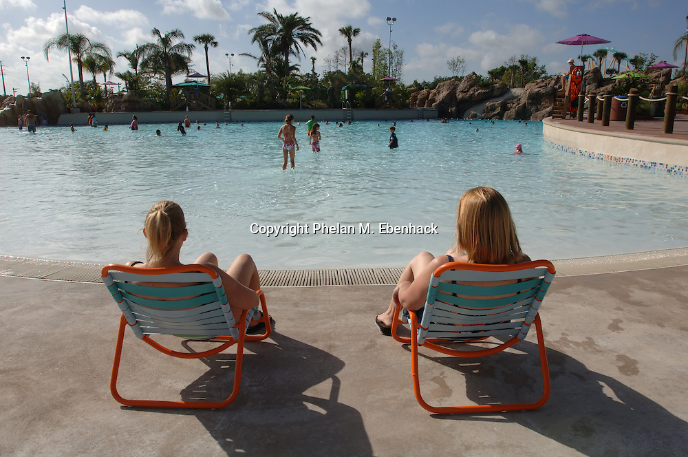 Two women soak in the sun on the edge of the Big Surf Shores wave pool at Sea World's new waterpark Aquatica in Orlando, Fla., Friday, April 4, 2008.