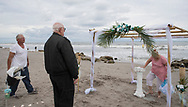 Tim Richmond (left) Scott Thatcher, and Cherie Richmond work on the gazebo for the wedding on January 20, 2018 in Jupiter, Florida.