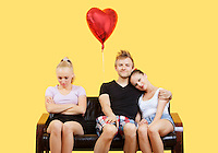 Portrait of young couple sitting on sofa with female friend feeling left out over yellow background
