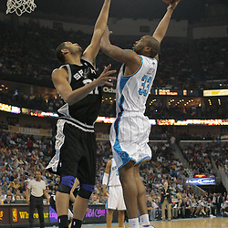 29 March 2009: New Orleans Hornets center Melvin Ely (33) shoots over San Antonio Spurs center Tim Duncan (21) during a NBA game between Southwestern Conference rivals the New Orleans Hornets and the San Antonio Spurs at the New Orleans Arena in New Orleans, Louisiana.