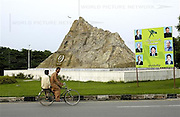 Two men ride on a bicycle infront of the monument to Chagi Mountain, the site of Pakistan's first series of nuclear tests, in Islamabad, Pakistan on Wednesday Aug. 9, 2006.