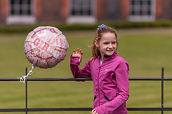 © Licensed to London News Pictures. 03/05/2015. London, UK. A girl poses with a balloon tied to a railing outside the Golden Gates at Kensington Palace for the new daughter of the Duke and Duchess of Cambridge who was born the previous day. Photo credit : Stephen Chung/LNP