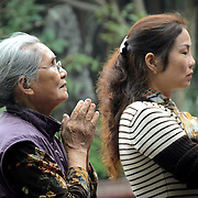 Two women pray at the Temple of the Jade Mountain (Ngoc Son Temple) on Hoan Kiem Lake in the heart of Hanoi's Old Quarter. The temple was established on the small Jade Island near the northern shore of the lake in the 18th century and is in honor of the 13-century military leader Tran Hung Dao.