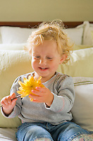 An 18 month old girl toddler smiling and looking at a flower
