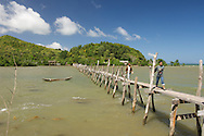 Two men cross a rickety hand made bridge on Palawan island in Taytay, Philippines.