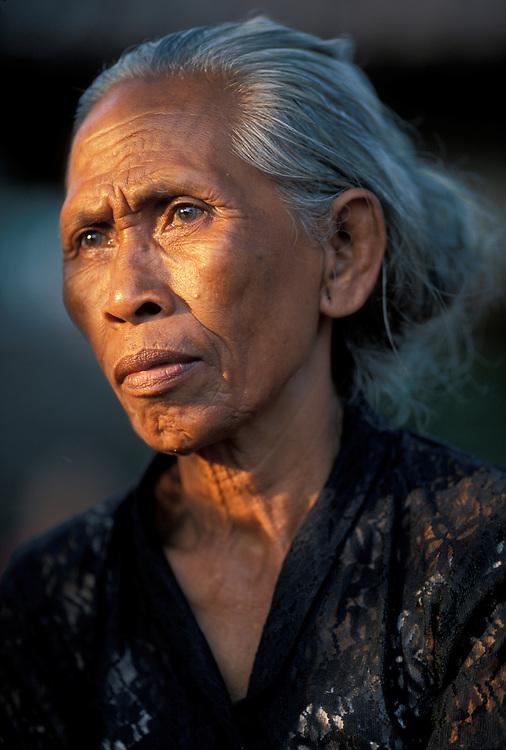 (MR) Indonesia, Bali, Elderly Female Mourner at Hindu Cremation ceremony in Gianyar