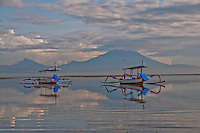 Two outriggerss on the sea with Agung and Batur seen at dawn from Sanur in Bali, Indonesia
