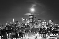 The setting moon over the Calgary city skyline just before sunrise on March 23, 2016.<br /> <br /> &copy;2016, Sean Phillips<br /> http://www.RiverwoodPhotography.com