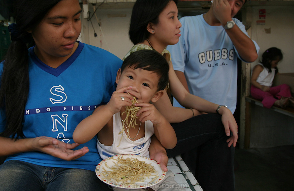 Young boy eats noodles by the fistful at a weekend festival in Manila. (Supporting image from the project Hungry Planet: What the World Eats)